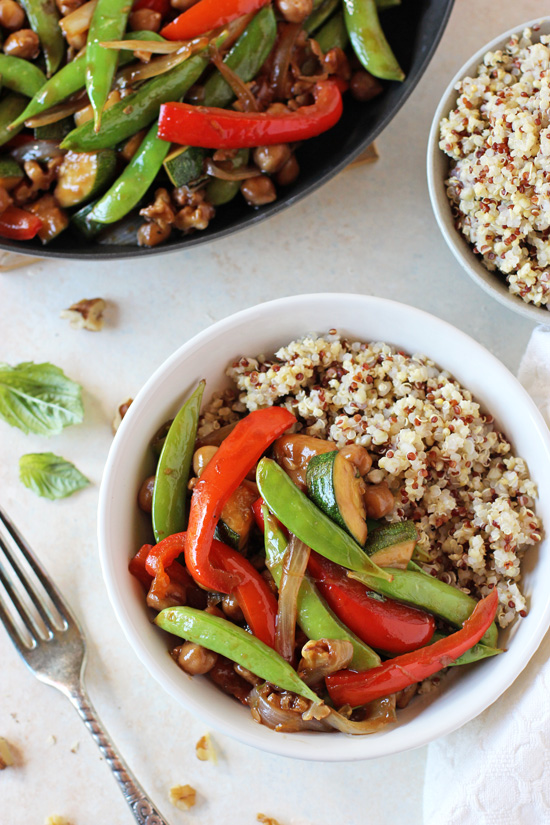 A white bowl filled with Zucchini Stir-Fry and cooked quinoa.