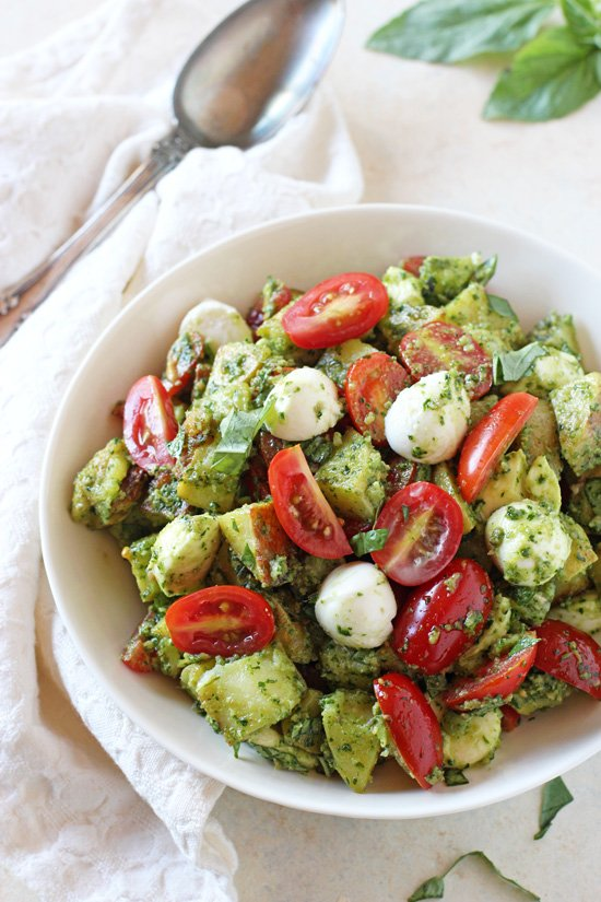 A white bowl filled with Caprese Pesto Potato Salad with a serving spoon to the side.