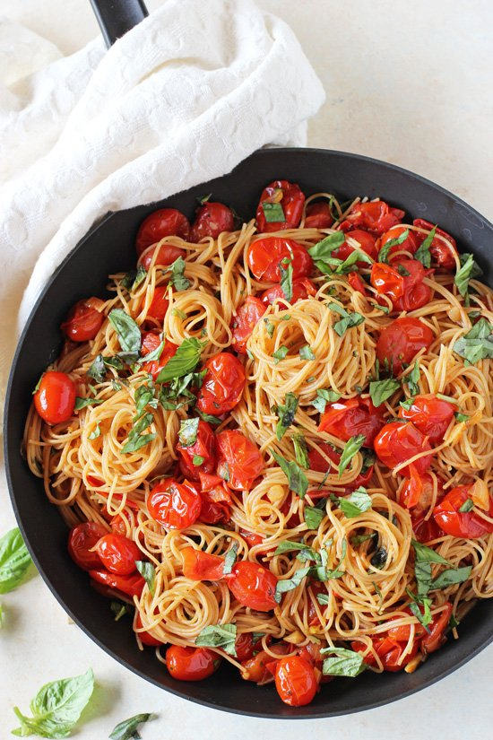 A black skillet filled with Cherry Tomato Sauce mixed with pasta.