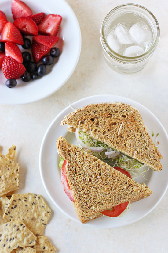 Overhead view of a Hummus Pesto Sandwich on a white plate with fruit and crackers to the side.