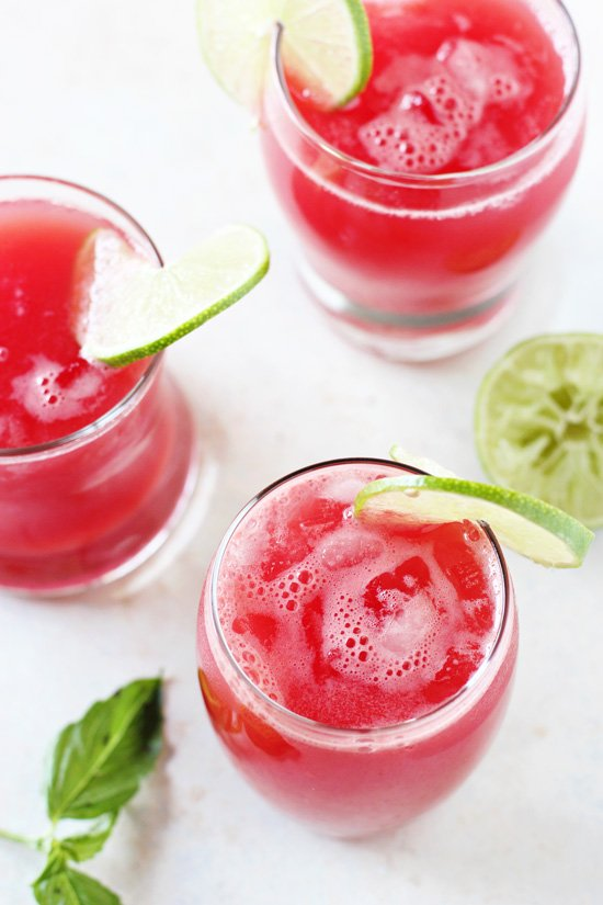 Three glasses of Watermelon Basil Agua Fresca with sliced limes on the rims.