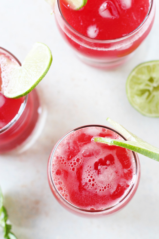 Overhead view of three glasses of Watermelon Agua Fresca with sliced limes on the rims.