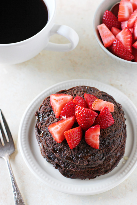 A stack of Chocolate Buckwheat Pancakes on a white plate with coffee and strawberries in the background.