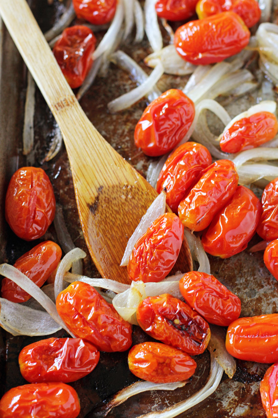 A baking sheet with roasted tomatoes, onions and a wooden spoon.