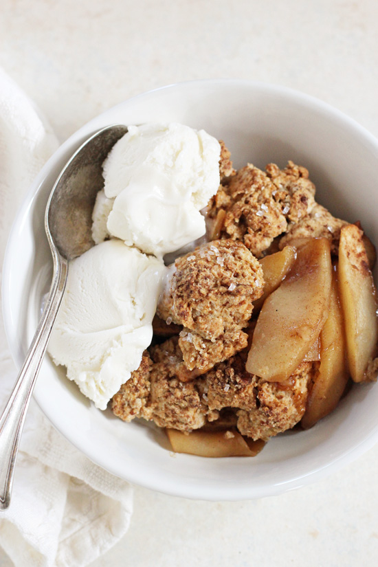 A white bowl filled with Vegan Apple Cobbler and topped with vanilla ice cream.