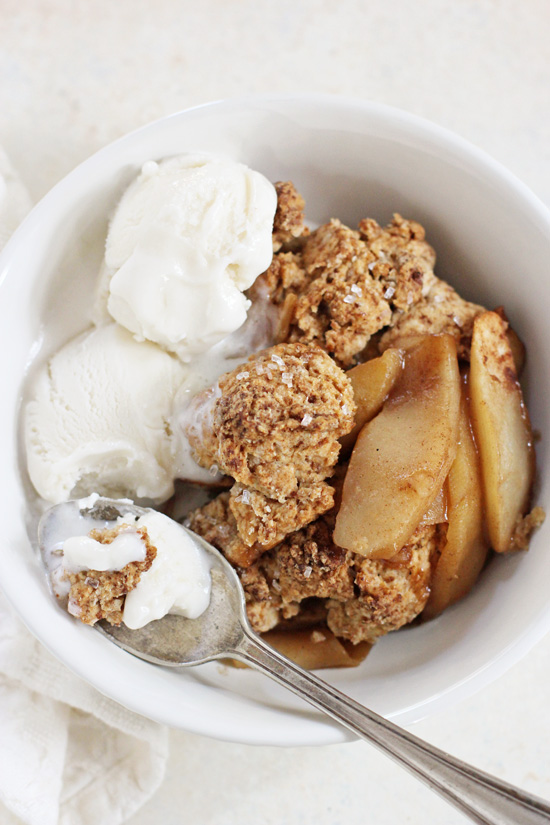 A white bowl filled with Vegan Apple Cobbler and a bite taken out with a spoon.