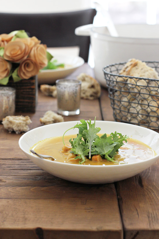 A bowl of soup on a wooden dining table with a bread basket and flowers in the background.