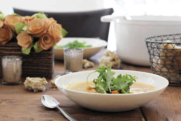 A wooden dining table filled with bowls of soup, flowers and a bread basket.