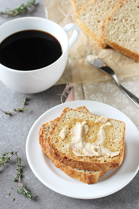 Two slices of Lemon Thyme English Muffin Bread on a white plate with coffee in the background.