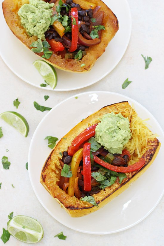 Two stuffed Mexican Spaghetti Squash on white plates with lime slices.