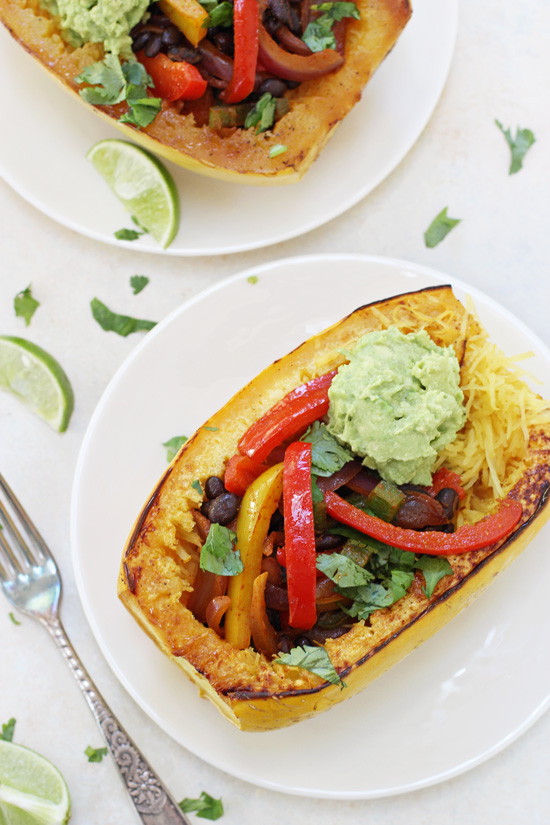 Overhead view of two stuffed Mexican Spaghetti Squash on white plates with a fork to the side.