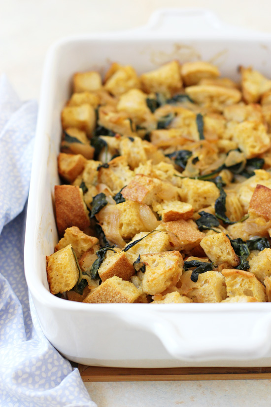 A white baking dish filled with Caramelized Onion and Spinach Stuffing.
