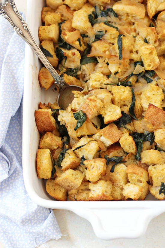 Overhead view of a tray of Caramelized Onion and Spinach Stuffing with a silver spoon in the dish.