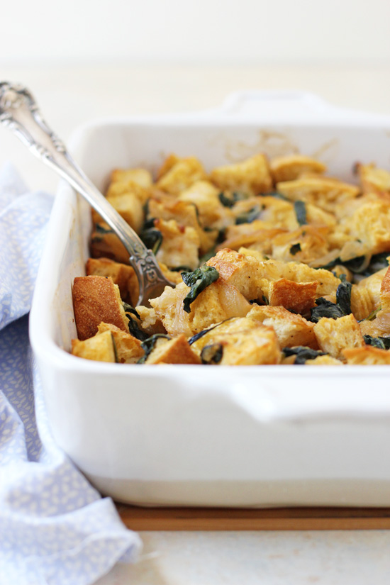 A white baking dish with Caramelized Onion and Spinach Stuffing with a serving spoon in the pan.