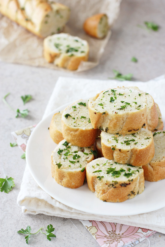 Slices of Homemade Freezer Garlic Bread stacked on a white plate.