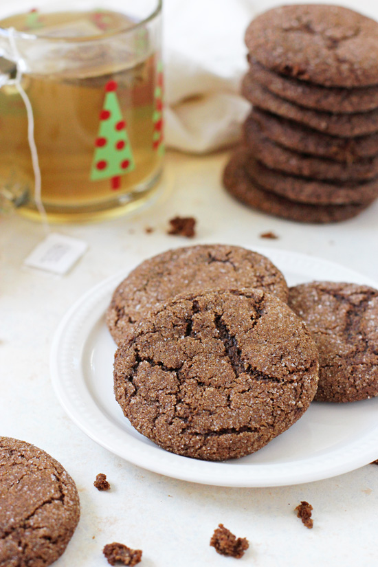 Three Soft & Chewy Whole Wheat Gingerbread Cookies on a white plate with more cookies and a cup of tea in the background.