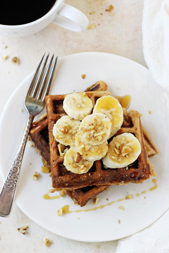 A white plate with two Healthy Banana Walnut Waffles topped with sliced banana and a fork on the plate.
