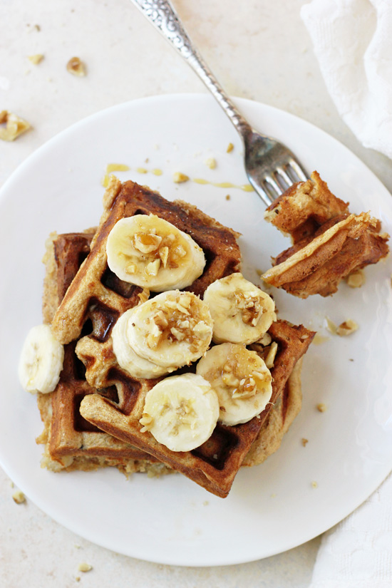Overhead view of two Healthy Banana Walnut Waffles on a plate with a bite taken out with a fork.