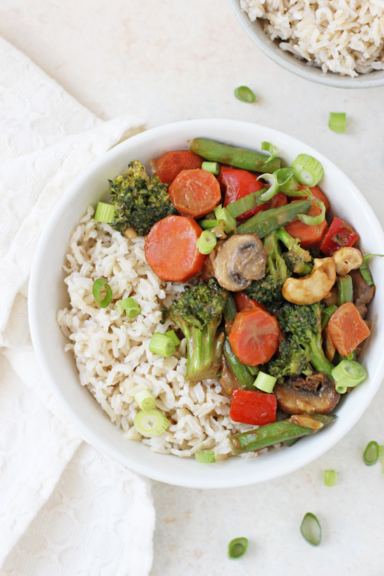 A bowl of Peanut Ginger Vegetable Stir-Fry with brown rice and a white napkin to the side.