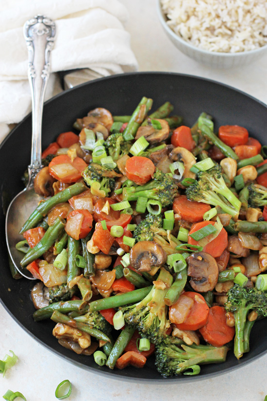 A skillet filled with Peanut Ginger Vegetable Stir-Fry and a silver serving spoon in the pan.