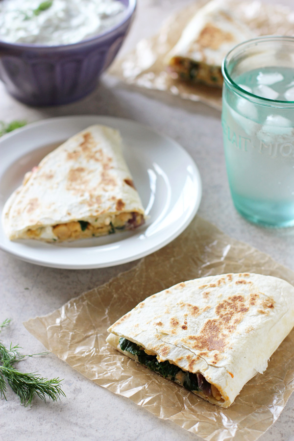 Three triangles of Greek Chickpea Quesadillas with a bowl of tzatziki and a glass of water to the side.