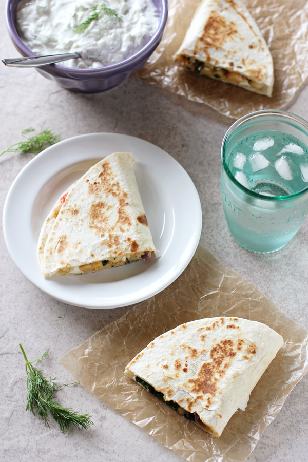 Overhead view of three triangles of Greek Chickpea Quesadillas with tzatziki and a glass of water to the side.