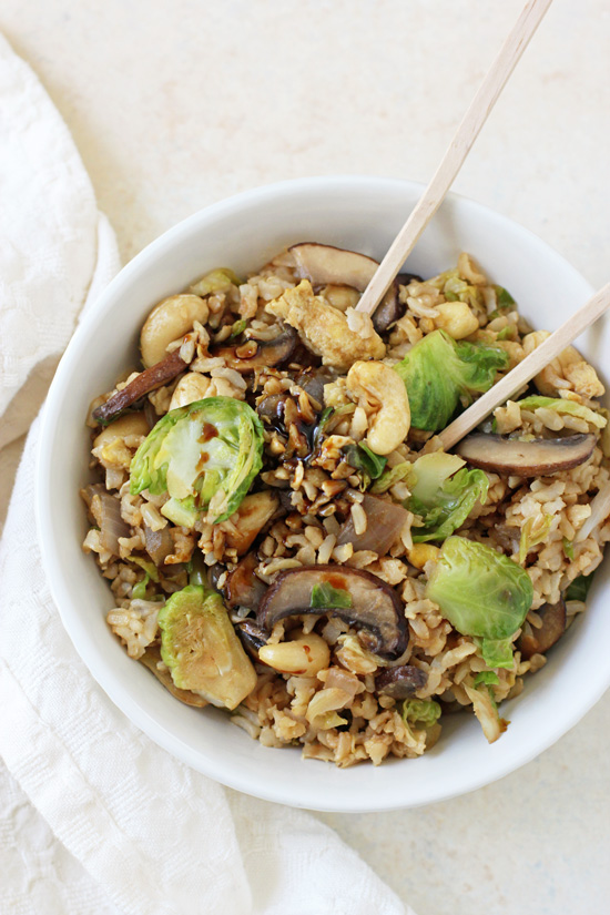 Brussels Sprout Fried Brown Rice in a white bowl with chopsticks and a napkin to the side.