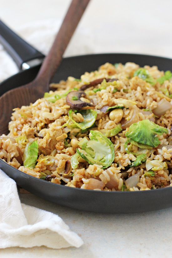 Side angle view of Brussels Sprout Fried Brown Rice in a skillet with a wooden spoon and napkin to the side.