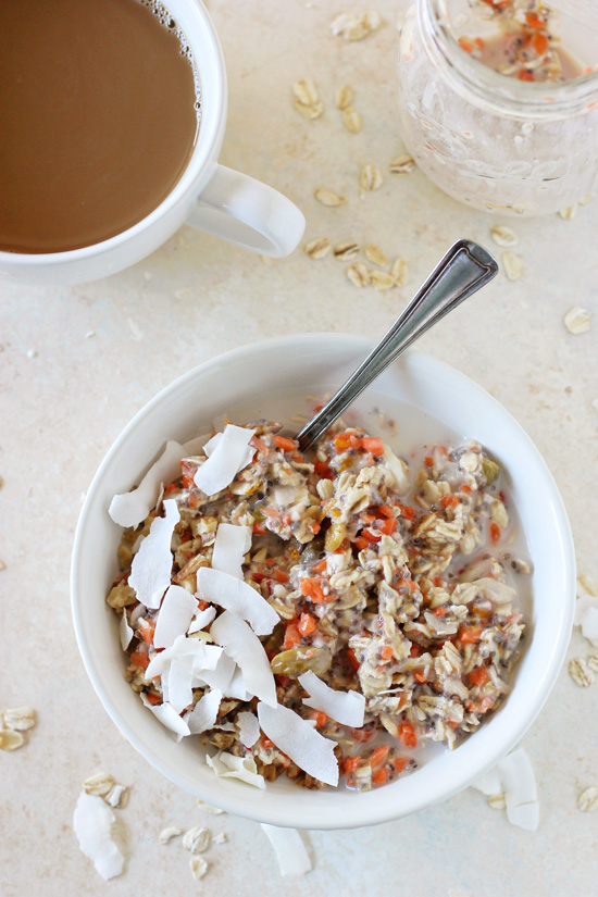 Morning Glory Overnight Oats in a white bowl with a spoon and a cup of coffee to the side.