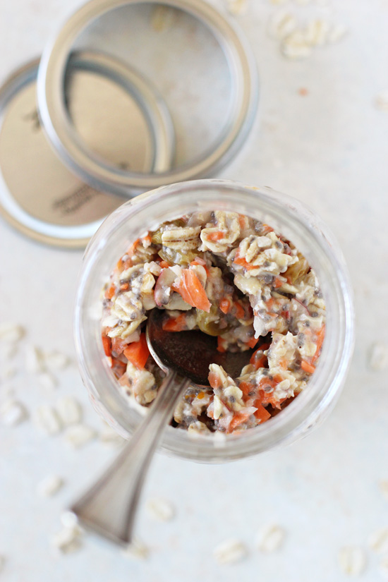 Overhead view of Morning Glory Overnight Oats in a glass jar with a spoon.