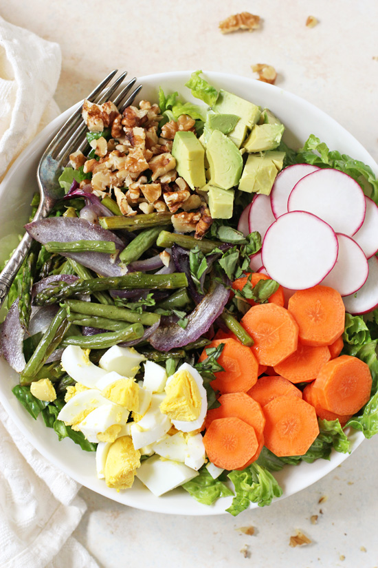 A white bowl filled with Spring Vegetable Cobb Salad and a fork and napkin to the side.