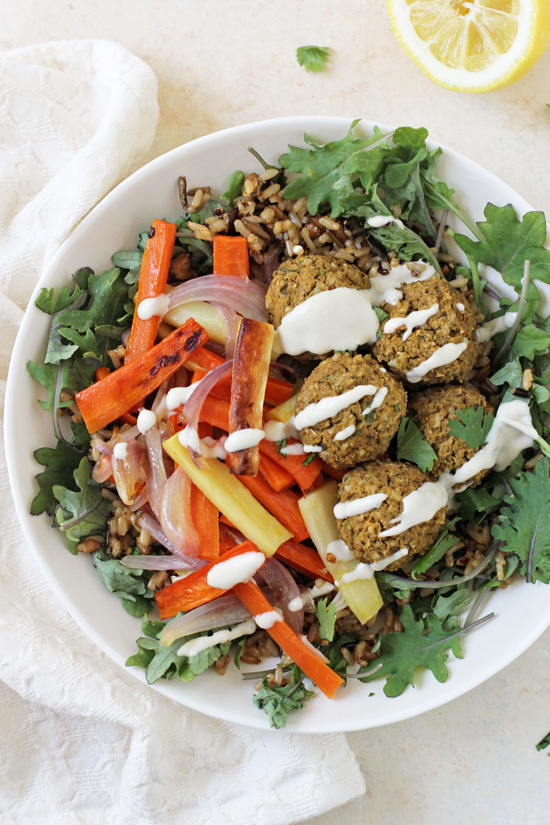 Baked Sweet Potato Falafel in a bowl with roasted veggies and greens.