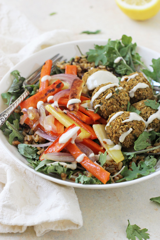 A side angle view of Baked Sweet Potato Falafel in a bowl with a fork and napkin to the side.