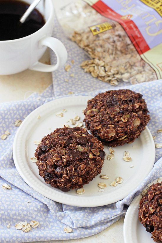 Side angle view of two Chocolate Breakfast Cookies on a plate with coffee and a bag of oats in the background.