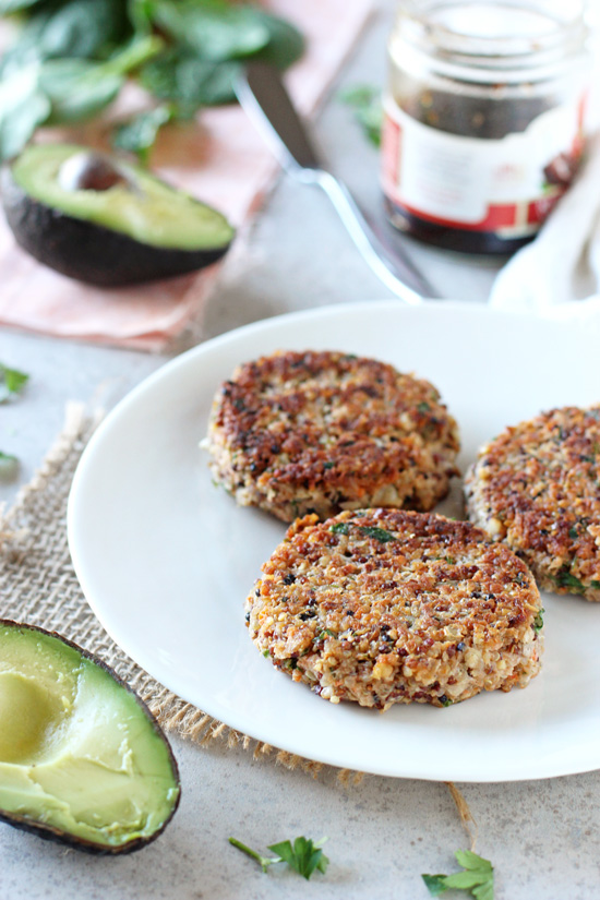 Three Fresh Herb and Roasted Garlic Quinoa Burgers on a plate with avocado and pepper jelly in the background.