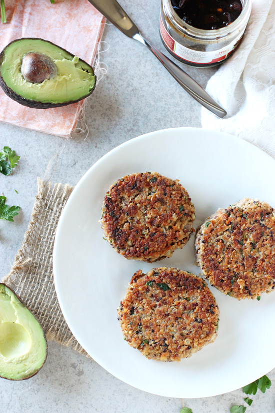 Overhead view of three Quinoa Veggie Burgers on a plate with avocado and pepper jelly to the side.