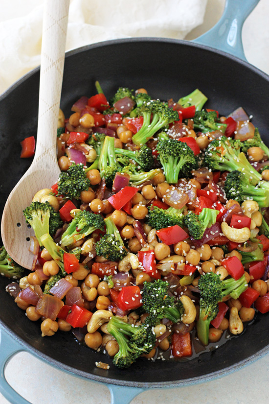 A skillet filled with Orange Chickpea and Broccoli Stir-Fry and a wooden spoon.