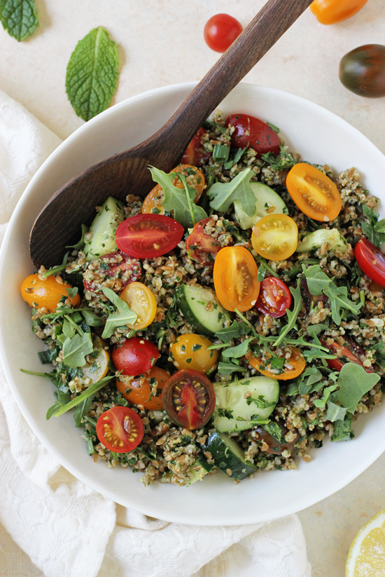 A white bowl filled with Pesto Tabbouleh Summer Salad and a wooden spoon.