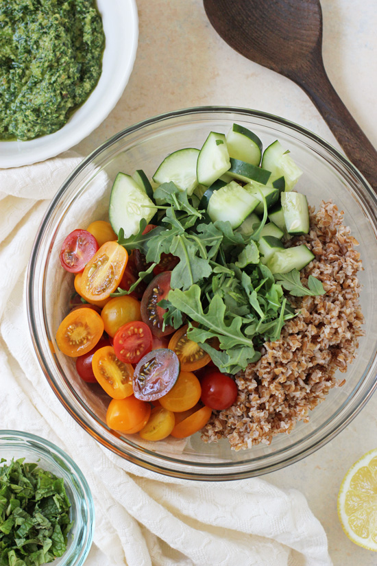 A glass bowl with bulgur, cucumber, arugula and tomatoes and a bowl of pesto to the side.