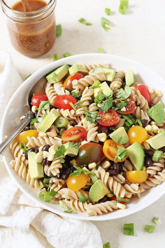 A bowl filled with Vegetable Taco Pasta Salad with a serving spoon and a jar of dressing in the background.