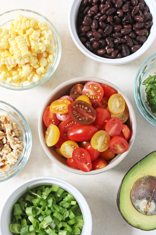 Small bowls filled with cherry tomatoes, black beans, corn kernels, walnuts and green onion.