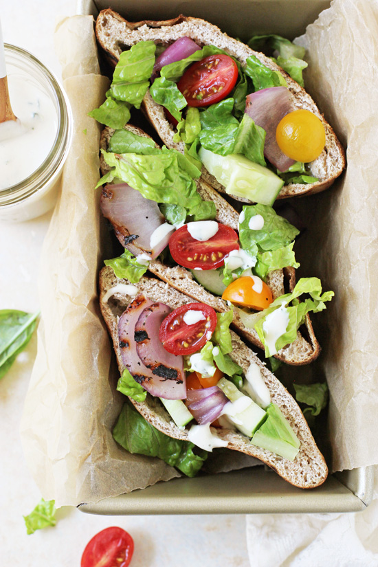 Grilled Greek Salad Pita Sandwiches stacked in a loaf pan with tahini sauce to the side.
