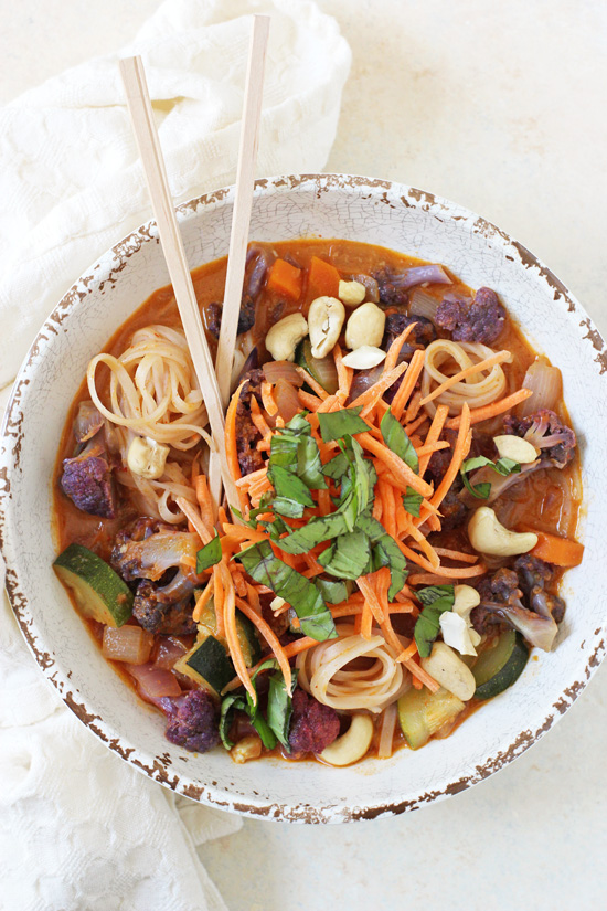 A Rainbow Vegetable Curry Noodle Bowl with chopsticks and a white napkin.