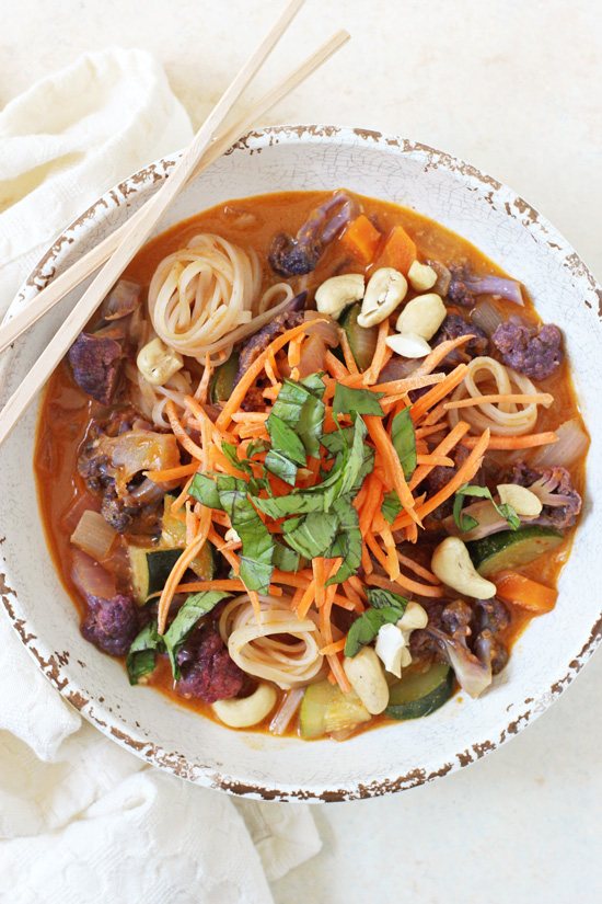 Overhead view of a Rainbow Vegetable Curry Noodle Bowl with chopsticks balanced on the side of the bowl.