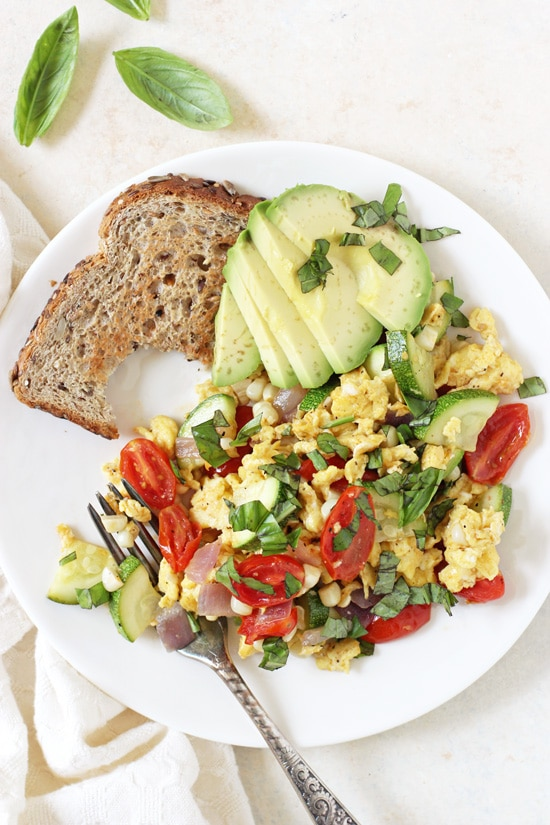 Summer Veggie Egg Scramble on a plate with a piece of bread and sliced avocado.