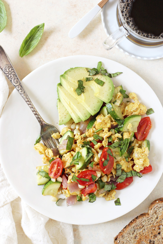 Overhead view of Summer Veggie Egg Scramble on a plate with a fork and a cup of coffee to the side.