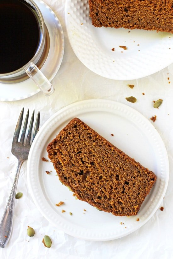 Two slices of Pumpkin Olive Oil Bread with a cup of coffee and a fork.