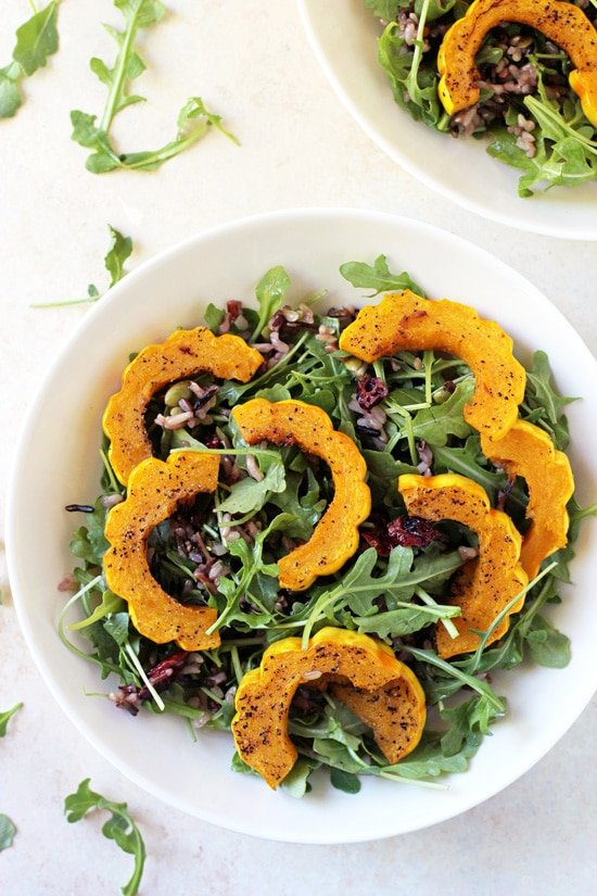 Two white bowls filled with Roasted Delicata Squash & Wild Rice Salad.