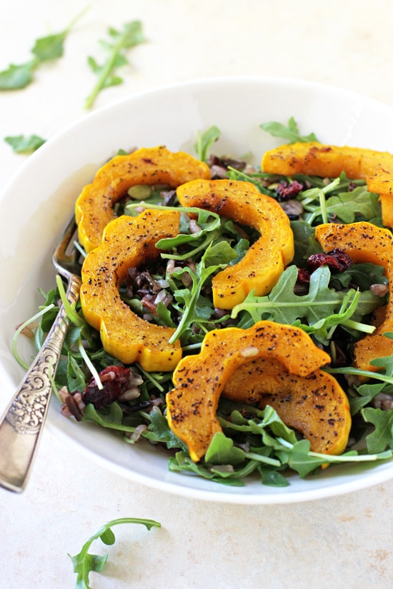 A side angle view of Roasted Delicata Squash & Wild Rice Salad in a white bowl with a fork.