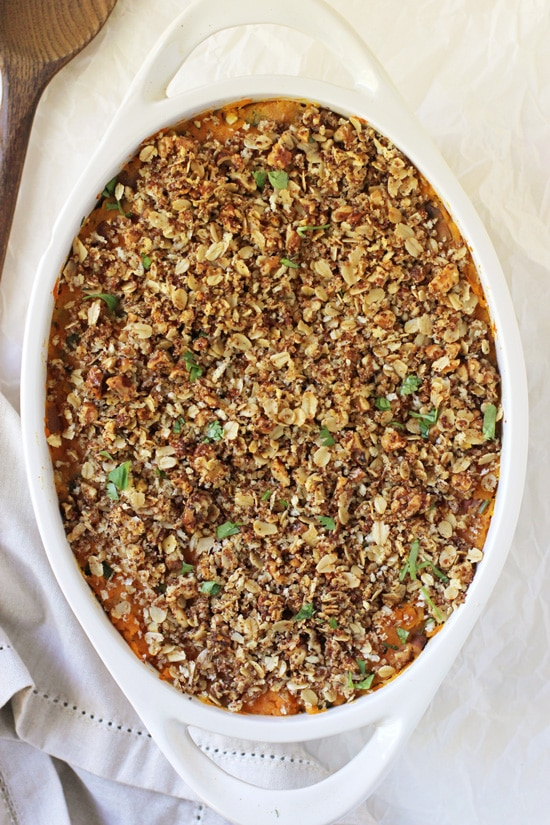 An overhead view of Savory Sweet Potato Casserole in a white baking dish with a wooden spoon to the side.